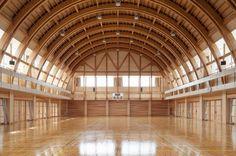 靜岡縣立湖北高等學校的多目的體育館,與一般的體育館非常不同,竹下一級建築士事務所大量使用靜岡縣產的杉木,為了確保運動比賽時所需要的挑高空間,將屋頂設計為像石橋般的圓拱狀,肋拱以每2公尺的樑間隔,創造出連續的木結構之美。 如此巨大又纖細的拱型木結構,為學校的運動空間打造出理想的環境。 via 株式会社 竹下一級建築士事務所