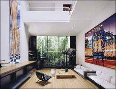 Rudolph built a greenhouse in what would have been the backyard. Halston then put in bamboo—and a mirror on the greenhouse's back wall. Right, the catwalk leads to a guest bedroom. In the living room are Sachs's photographs Crazy New York and Skyscraper, left, both featuring model Kirstin Kober, and some photo equipment.   (Photo credit: Nikolas Koenig)