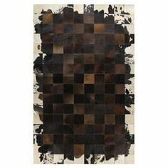 Hand-stitched cowhide rug with a patchwork motif and asymmetrical contrast border.   Product: RugConstruction Material: CowhideColor: ChocolateFeatures: Hand-stitched Note: Please be aware that actual colors may vary from those shown on your screen. Accent rugs may also not show the entire pattern that the corresponding area rugs have.Cleaning and Care: Vacuum regularly. Spot clean.