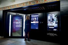 """The Intelligent Color Experience vending machine has screens and a full-length mirror that uses cameras and sensors to suggest L'Oreal products to passersby. The machine presents customers with a digital animation of their silhouette and the colors they're wearing, and asks if they want cosmetics that """"match"""" or """"clash."""""""