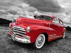 A classic red Chevrolet car with white wall tires. This vintage 1948 chevy is a great example of forties American muscle cars #americanmuscle #musclecars #hotrods #coolcars