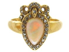 An original Victorian heart ring in opal and yellow gold.  There are many copies on the market which are quite crude when subjected to examination. This ring has a shaped opal set to the centre and surrounded by small rose-cut diamonds.