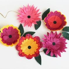 Learn how to create a pretty flower garland with cupcake cases and string.