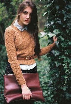 white/blue collared shirt; tan cable knit pullover; black pants