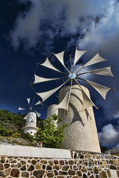Towering Creton Windmills on the Lasithi Plateau in north eastern Crete against a vivid blue sky and puff white clouds, Ideal for the kitchen, rec room, lobby or hotel room. Sip a class of ouzo and enjoy this classic Greek windmill scene