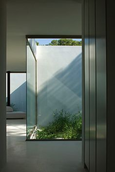 Glass walls and small patio, interior of the Ibicaelum House in Spain by Bruno Erpicum / Aabe ( © Jean-Luc Laloux) _