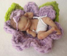 Hand sculpted baby girl in lavender flower.   Handsculpted by Lisa Haldeman ~ Lovinclaydolls