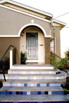 Curb Appeal designer John Gidding ties in a traditional front door with a Mediterranean curb appeal design using a blue hue similar to the tiles used in the front stair risers. Front Door Plants, Green Front Doors, Front Door Paint Colors, Painted Front Doors, Porch Styles, House Styles, Front Porch Stairs, Exterior Color Palette, Traditional Front Doors