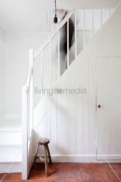 Stauraum im Einbauschrank unter weisser schlichter Landhaustreppe mit hinabgehender Person und Schemel auf Terracottaboden – living4media