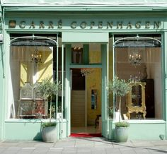 I love this shop. The color, the chandeliers, the topiary. Adorable.