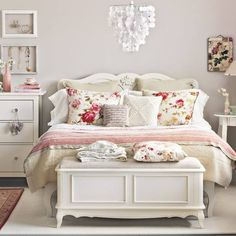 pretty bedroom It's the rose print pillows, the bed layers, the unmatched style yet color match of side tables, Pretty rose print on wall, stack of books, & pretties on the table