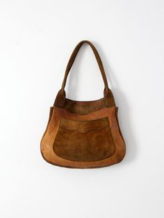 1970s Great patina! This is a vintage suede leather shoulder bag. Beautifully aged, tan leather and suede shapes the bag. It features a suede back, sides, front pocket, and handles with a leather face