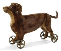 A STEIFF VELVET DACHSHUND ON WHEELS, (12M), brown with cream belly and chest, black boot button eyes, brown stitching, gold painted cast metal wheels, axle through feet and elephant button, circa 1904 --6¼in. (16cm.) long (some slight wear and discolouration)