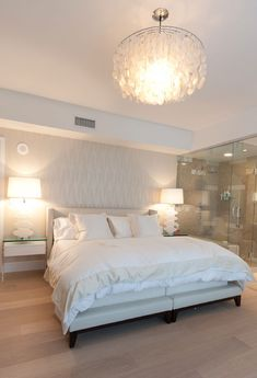 All the white and  the light wood floors in this room help give the room a luxorious feel