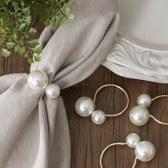 With a sleek, polished ring and oversized pearl accents, these napkin rings are an easy way to add a dash of elegance to your table. Set of four.