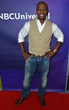 Terry Crews sports a khaki vest, white button down, jeans
