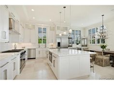 Gorgeous white transitional contemporary kitchen with huge center island, eat in, wine bottle chandelier - Connors Vanderbilt Beach in Naples, Florida
