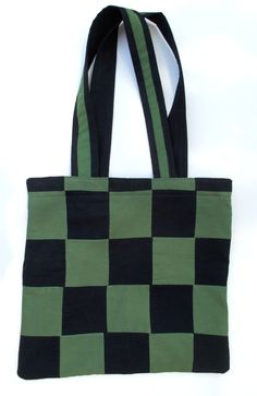 Green Checkered Tote Bag. Handmade cotton tote bag sewn with a solid green and black fabric with a double layered lining. Inside lining is black. Checkered pattern. Each square is sewn together individually. No pocket inside. Lightweight tote bag  Bag is approximately 14.75 inches (height) and 15.25 inches (width). Straps are 27 inches in length and measures approximately 12.5 inches from the top of the bag. Straps are approx. 2 inches wide. Straps are black with a strip of green on one…