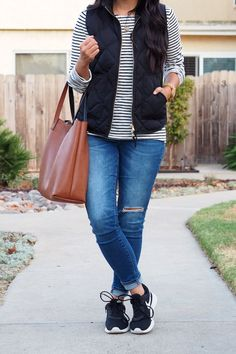 Casual Fall Outfit details: black vest + striped tee + distressed jeans + black sneakers