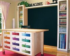 Love the glass-front drawers to organize by color. That's a black felt design wall in the background.