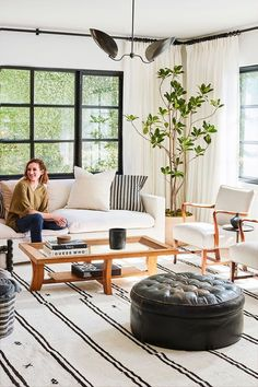 light white living room black windows pouf wood green houseplants couch modern natural design decor interior home house How to Choose a Rug for Your Home, According to Our CEO, Katherine Power via @MyDomaine