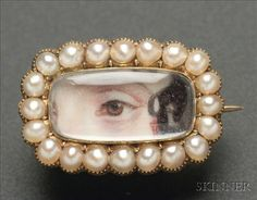"Miniature ""Lover's Eye"" Brooch, early 19th century, centered with a rectangular watercolor on ivory depiction of an eye with a brown iris, and a lock of brown hair, framed by small pearls in a gilt metal brooch., 4/8 x 7/8 in. Condition: Very good.    Sold for: $ 3,525"