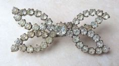 Vintage clear rhinestone studded butterfly brooch.  The butterfly is formed from clear rhinestones set in silver tone metal layers.
