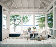 In the screened-in porch of this expansive Muskoka cottage, a comfortable outdoor daybed and cozy armchairs are covered in crisp white Sunbrella fabric, so it's both pretty and hard-wearing. | Photo: Michael Graydon