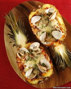 Roasted Seafood-Stuffed Pineapple Recipe -- pineapple halves are filled with shrimp, halibut, chopped pineapple, adobo sauce, Emmentaler cheese, and clams.