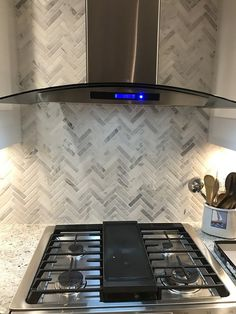 This white marble tile features a tumbled surface with subtle grey speckling and grey and tan veining that will bring distinctive style -  Hampton Carrara Tumbled Large Herringbone Marble Mosaic Tile