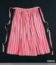 Åryd 185-1890 | Förkläde i bomull, randigt i vitt på rosa botten med dels smala tvåtrådsrändetr, dels med jämna mellanrum något bredare med  hoptvinnat vitt och rosa garn som ger flamgarnseffekt. . Smala fållar i nederkant och båda sidor, upptill rynkat mot  3 cm bred   midjelinning . Linningen  förlängd med fastsydda 2 cm breda  knytband  av bomull mönstervävda  i rosa på vit ripsbotten.