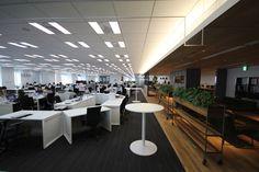 歌舞伎座タワー(中央区)の18階に集約した東京本部の執務スペース。視界の開けた空間に、扇形のデスクが並ぶ。立ったまま打ち合わせができる円テーブルは、執務スペースに8つ配置している(写真:ケンプラッツ)扇形レイアウトや席替えで活性化、クロスカンパニー|日経BP社 ケンプラッツ