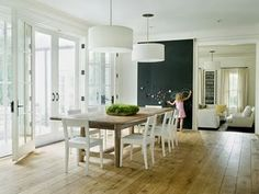 I LOVE this dining area White drum pendants, farmhouse dining table, white modern chairs, French doors, chalkboard wall and rustic wood floors. Table Design, Dining Room Design, Dining Area, Dining Rooms, Small Dining, Kitchen Dining, Kitchen Floor, Open Kitchen, Huge Kitchen