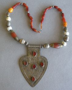 Traditional Turkman workmanship. | Afghani necklace with silver plaque, partially gold washed. 4 carnelian stones set in raised bevel. The necklace has been restrung with traditional beads of silver, carnelian, amber and bone.
