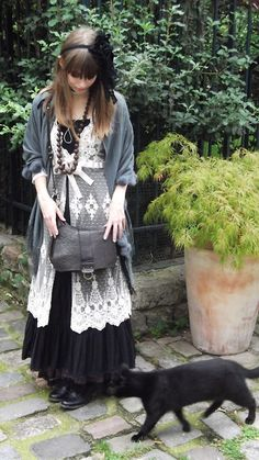 """So-called """"dark forest mori"""" gives traditionally light and airy mori style a saturated goth twist. Here, a familiarly mori white lace vest seems a spiderweb over the flared black maxi dress. The figure-concealing silhouette and emphasis on layering and natural hair and makeup are maintained from traditional mori, but this forest girl grows poison apples instead of sweet blossoms."""