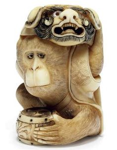 An Ivory Netsuke Signed Masatami, Edo Period (19th century) Of a monkey with a drum and a karashishi mask 9cm. high
