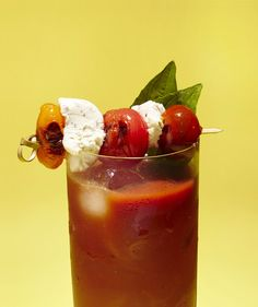 Thread roasted cherry tomatoes and bocconcini (mini fresh mozzarella) onto a large toothpick and rest it across the top of the glass. Garnish drink with a sprig of fresh basil.
