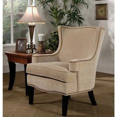 Bring sophistication and class to your living room with this Lorena Fabric Nailhead Trim Armchair.