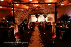 Beautiful Aisle with 100,000 silk petals and giant glass cylinders with silk flower kissing balls and bling arches over the aisle -- Blog tells all the behind the scenes -- www.EventProTraining.com