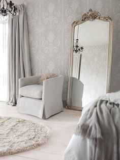 white, natural, light grey room with large gilt floor mirror, chandelier, dove grey drapes