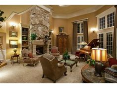 Love the height of this room with the stone fireplace and large windows!!