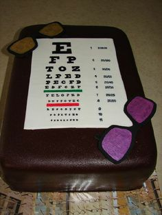 """Eye Chart cake - 9x13"""" French vanilla/milk chocolate cake, strawberry filling, French vanilla BC, Satin Ice chocolate fondant, sunglasses/eye chart/letters fondant. Gold and fuschia lustre dust for lenses. Made as a thank you for two friends who are eye drs and who gave us a deal on some sunglasses. Chocolate fondant was darker than I'd thought so sunglasses don't show up as well on camera as in person. Thanks for looking!"""
