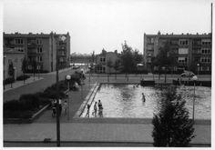 1959. Gezicht op een deel van het Herderplein te Utrecht met op de voorgrond de vijver; rechts op de achtergrond een gedeelte van een flatgebouw aan de Dickenslaan en links van het midden de La Fontainestraat met daarachter het Amsterdam-Rijnkanaal.