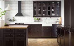 Perinteisen tyylinen, tummasävyinen keittiö, jossa massiivipuuta ja mustaa.