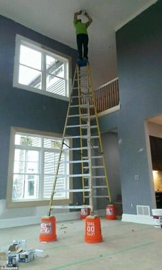Keep it steady: This electrician fits a smoke alarm on a high ceiling with his ladder plac...
