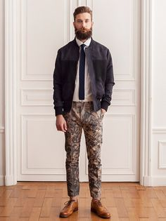 Black Baseball Style Jacket, Tie, and Olive and Tan Floral Chinos. Men's Spring Summer Fashion.