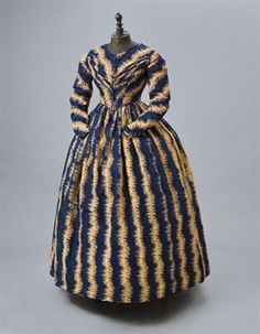 A PRINTED WOOL DAY DRESS   1840S   one piece of vivid blue with a red and honey-yellow trailing floral motif, the bodice with pointed waist, sloping shoulders and pleated detail across the bust, the skirts a gentle bell shape  25in. (63.5cm.) waist