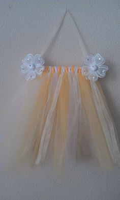 """This handmade hair bow holder has a very girly look which will work for baby through older girls. Its a soft delicate must have for the little lady with all the hair bows.  The ribbons hanging down are sheer yellow.  The holder is approx 18"""" from top of the hanger to the bottom of the tulle. It is approx 8.5"""" across. From dowel to bottom of tulle is approx 12"""" in length with 10 ribbons hanging to clip hair accessories to."""