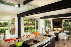 Large windows and doors create an open kitchen and dining area that seamlessly blend the indoors and out. Exposed black structural beams are a strong contrast against the white walls of the space, while an oversized kitchen island and sleek dining area make the space both family friendly and perfect for entertaining.