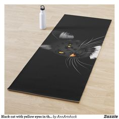 Black cat with yellow eyes in the dark yoga mat